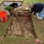 Two people digging at an archaeological site in the ground.