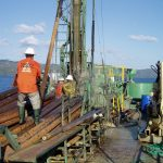 A person in an orange safety vest on a boat where sediment cores of the seafloor are being collected in large metal tubes.